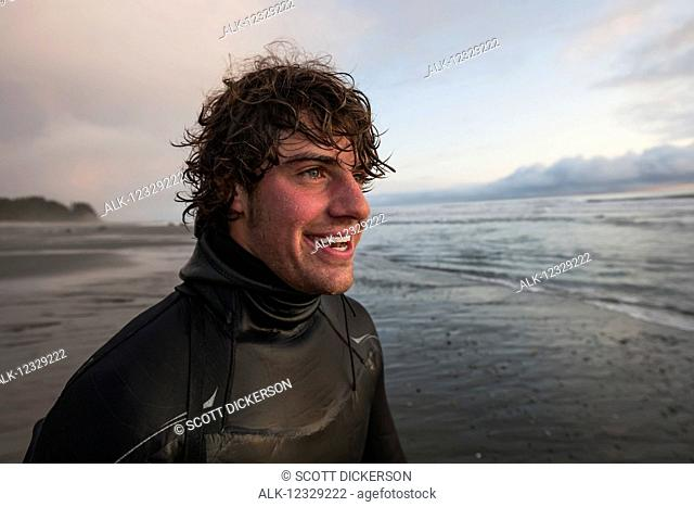 Portrait of a surfer along the coast near Yakutat, Southeast Alaska; Alaska, United States of America