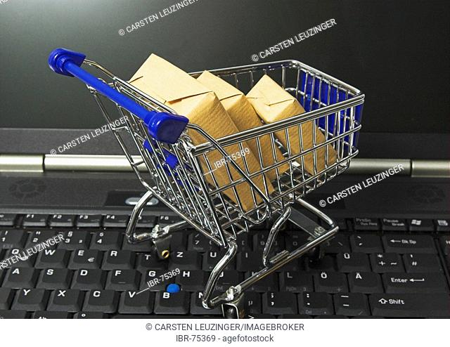 Online shopping, a shopping cart filled with parcel standing on the keyboard of a notebook computer