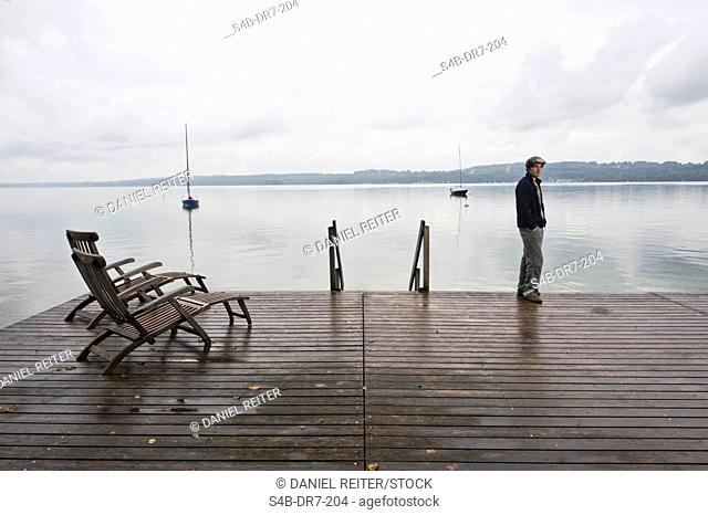 Man standing on jetty at Lake Starnberg, Bavaria, Germany
