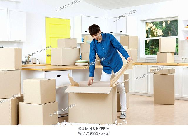 A man and a woman packing moving boxes in a kitchen