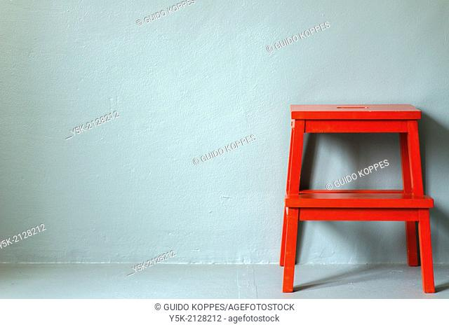 Tuinstraat, Tilburg, Netherlands. Small, red painted stool, bought at Ikea, parked against a grey photo-studio wall