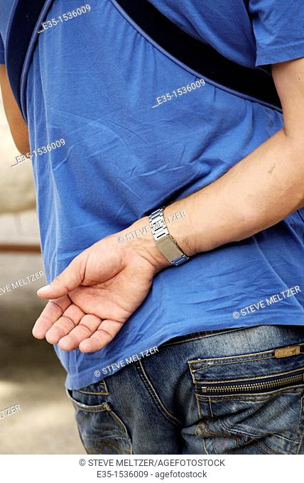 A man stands with his arm behind his back, a typical French gesture