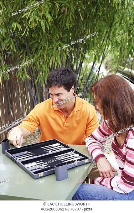 High angle view of a mature woman and a mature man playing backgammon