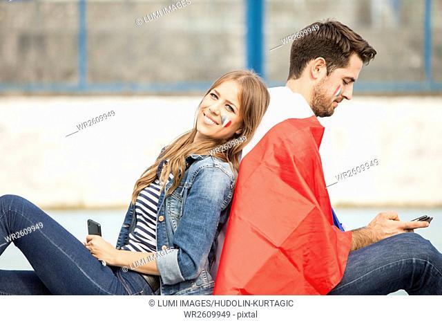 Male soccer fan and girlfriend sitting back to back