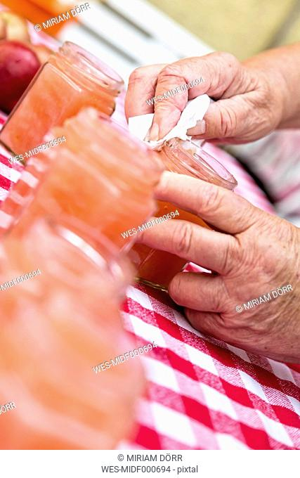 Senior woman wiping glass of homemade applesauce, close-up