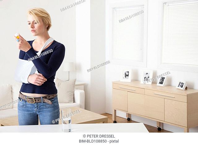 Caucasian woman with broken arm reading pill bottle