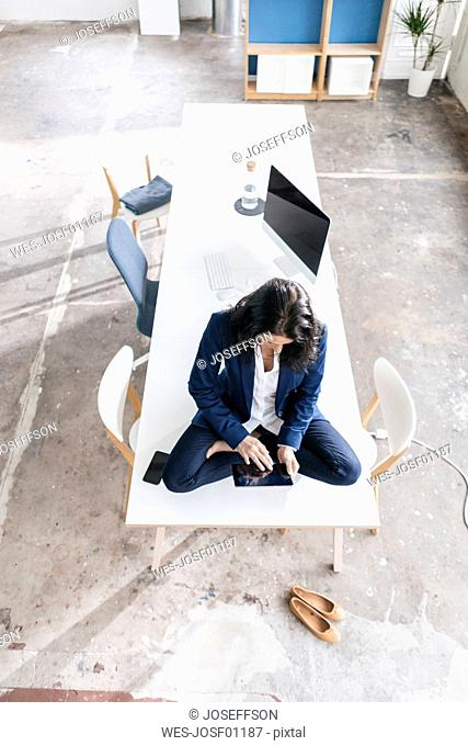 Businesswoman sitting on desk in a loft using tablet