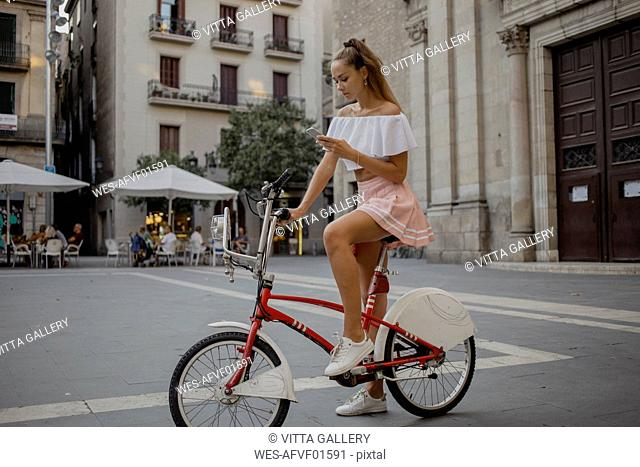 Fashionable young woman exploring Barcelona with a bicycle, using smartphone