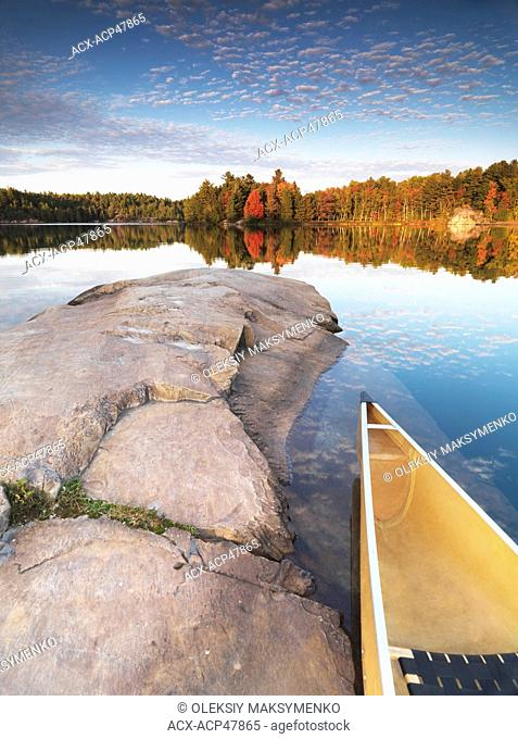 Canoe at a rocky shore of lake George. Beautiful sunset fall nature scenery. Killarney Provincial Park, Ontario, Canada
