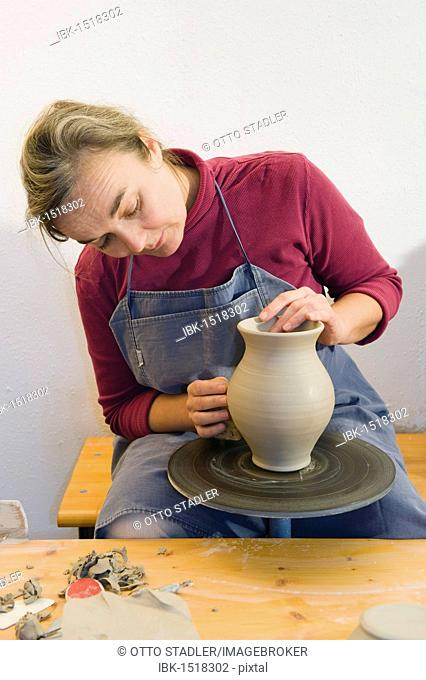 Ceramic artist working in her workshop with a potter's wheel, polishing the surface of a pitcher, Geisenhausen, Bavaria, Germany, Europe