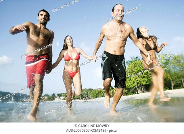 Two mid adult couples running on the beach