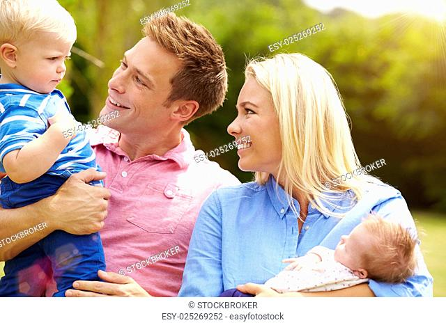Parents Holding Young Children In Garden
