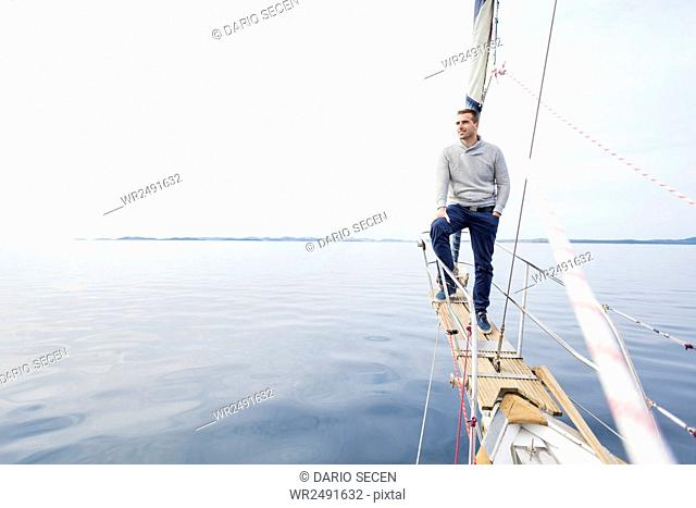 Man stands on bow of yacht day looking at sea