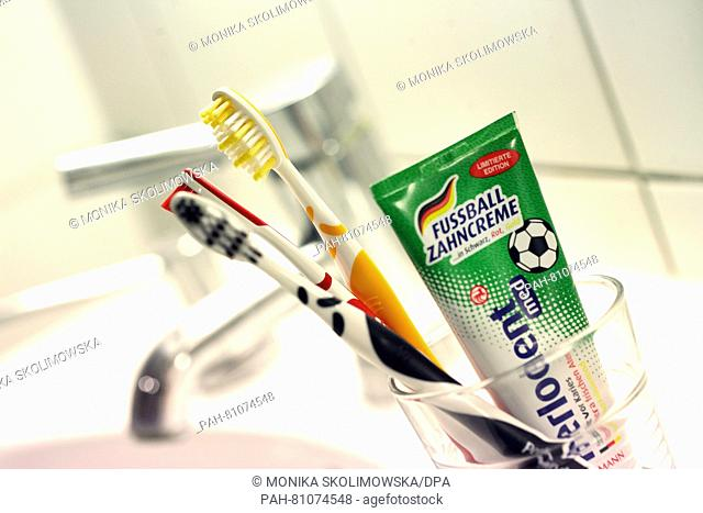 ILLUSTRATION - Black-red-gold toothpaste and three toothbrushes in the German national colors sit in a glass in Berlin, Germany, 09 June 2016