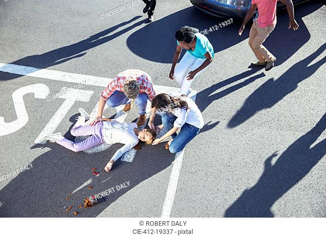 People examining injured girl on street