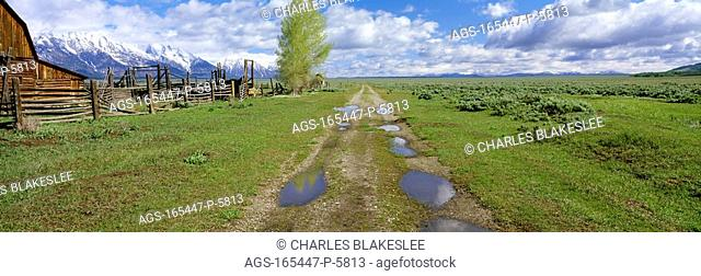 Agriculture - Gravel ranch road and barn, with the snow capped Grand Teton mountains on the left / WY - Teton County