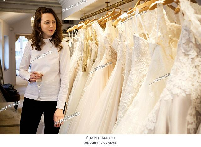 Rows of wedding dresses on display in a specialist wedding dress shop. A woman holding a glass of champagne looking at a rack of couture gowns with lace and net