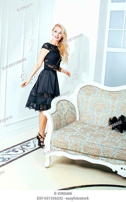 stylish elegant blonde woman in beauty rich interior, wearing black dress smiling celebration
