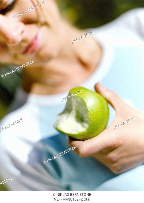 A woman eating a green apple