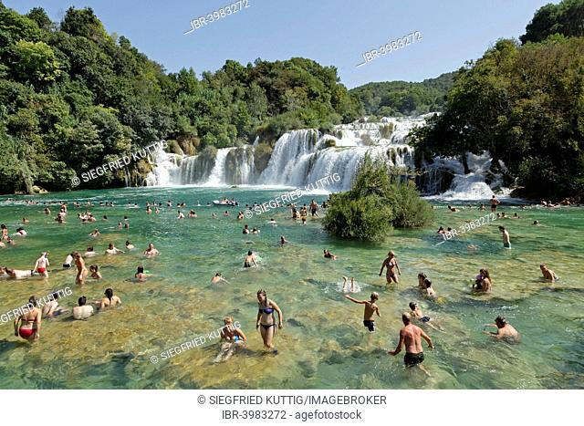 People swimming in front of a waterfall, Krka National Park, Dalmatia, Croatia