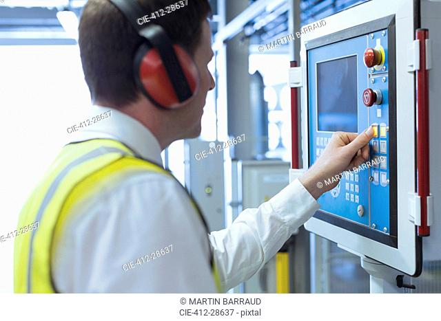 Worker with ear protectors at control panel in machinery