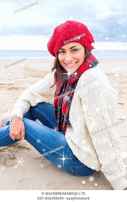 Smiling woman in stylish warm clothing sitting on beach against snow falling