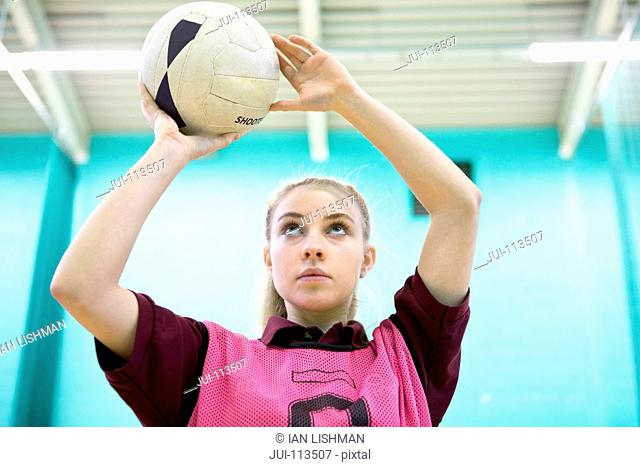 Focused high school student playing netball in gym class