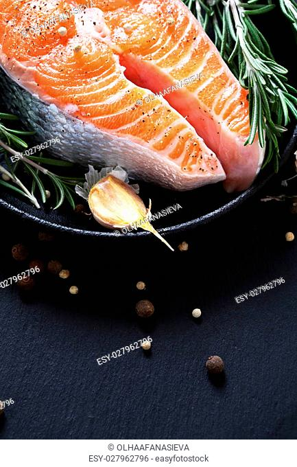 Salmon and spice in pan on slate, tasty food