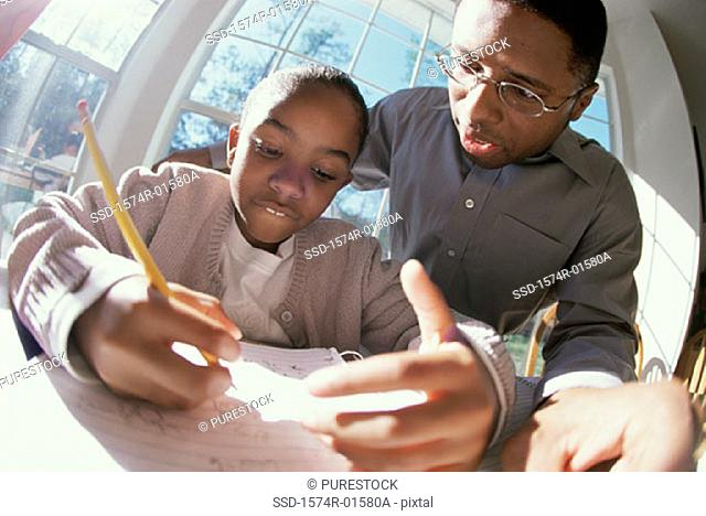 Father helping his daughter with her homework
