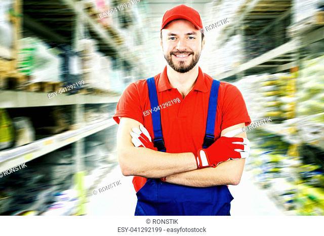 smiling warehouse worker standing between shelves
