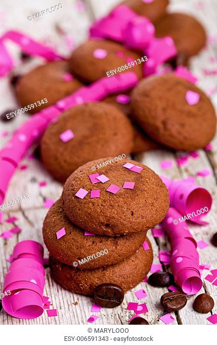 fresh chocolate cookies, coffee beans, pink ribbons and confetti on rustic wooden background