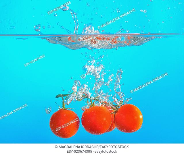 red tomatoes dropped into water isolated