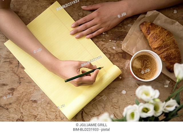 Hispanic woman writing on yellow notepad at breakfast