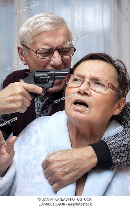 Mad senior couple fighting with a gun