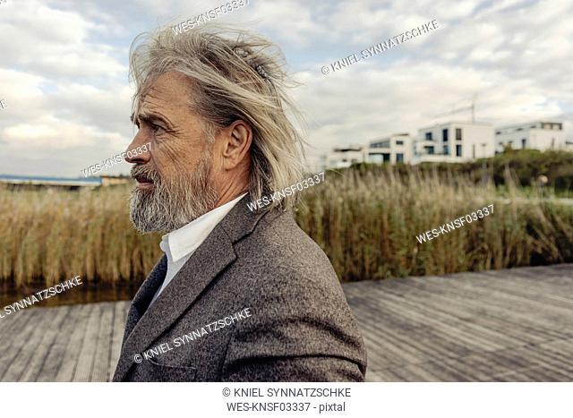 Portrait of serious senior man at lakeshore