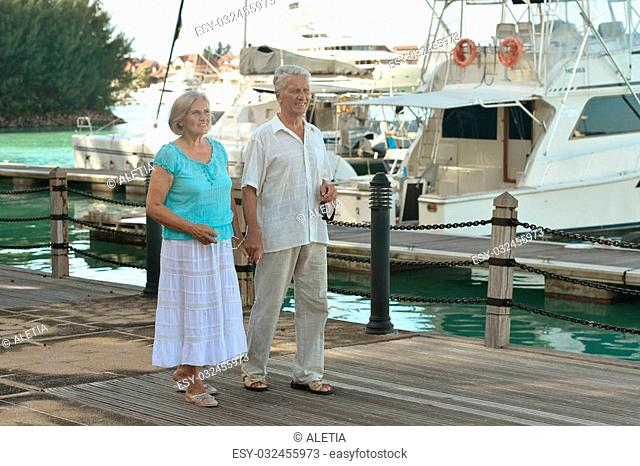 Happy cute senior couple on the pier with yachts