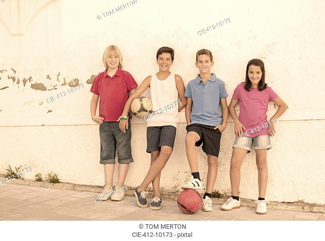 Children with soccer balls leaning against wall