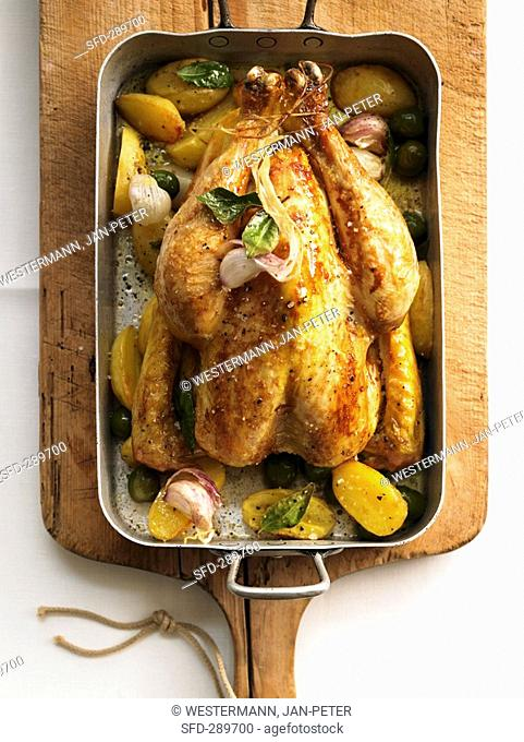 Roast chicken with bay leaves, olives and potatoes