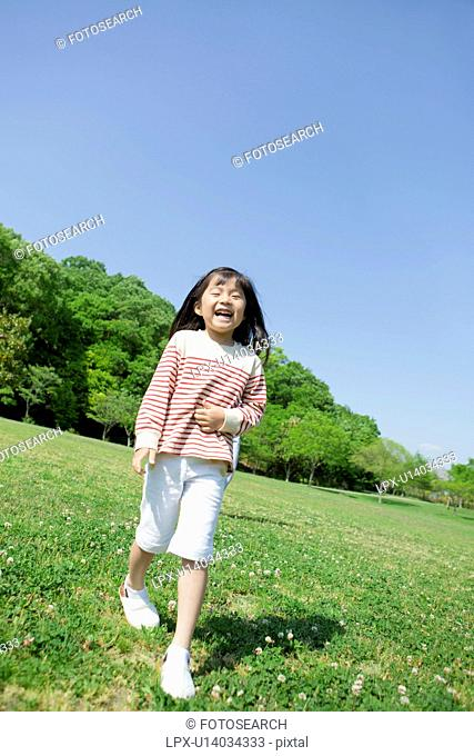 Girl standing and smiling at a park