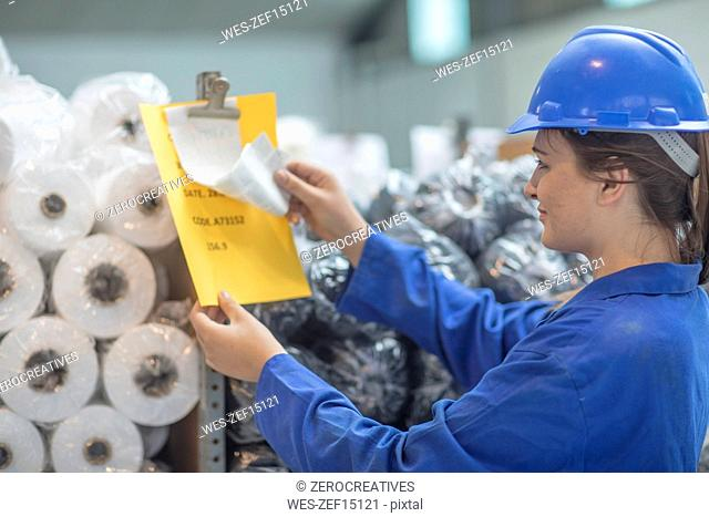 Woman wearing hard hat checking document in factory