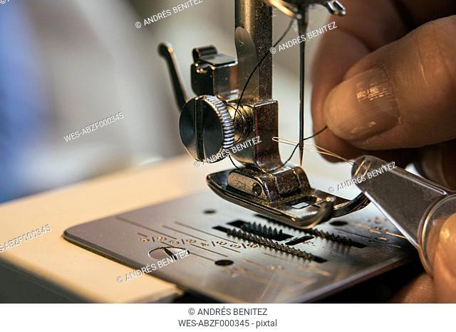 Woman adjusting thread in a sewing machine