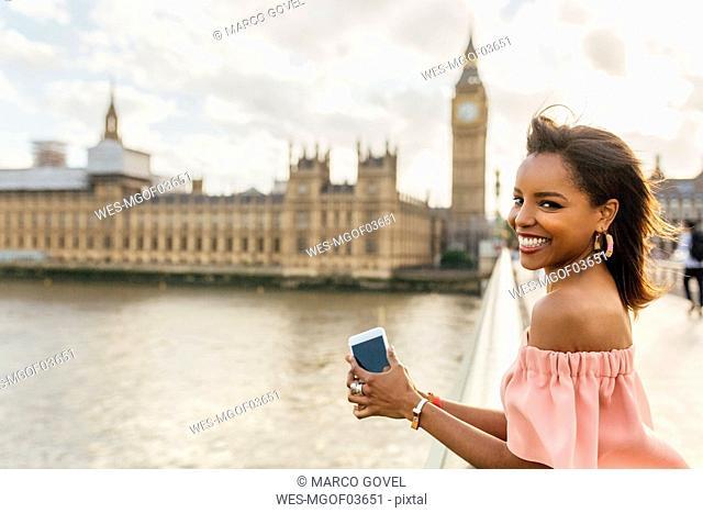 UK, London, portrait of smiling woman on Westminster Bridge