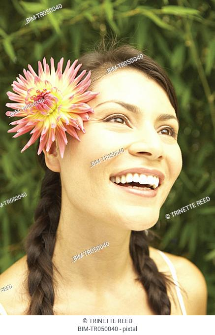 Portrait of woman smiling with flower in hair