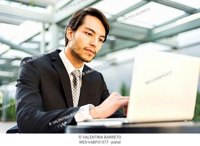 Businessman working on laptop outdoors