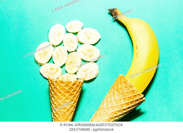 Close up of two waffle cones with fresh banana and sliced banana lying on bright green background