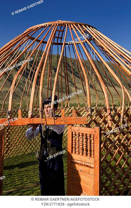 Man in traditional clothes tying the wood frame of a Yurt in Saty Kazakhstan