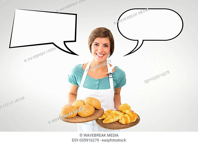 Happy small business owner woman with speech bubbles holding pastries against grey background