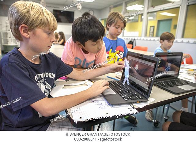 Caucasian and Asian American boys work at laptops in a Boys and Girls Club computer lab in Laguna Beach, CA. Note cutouts