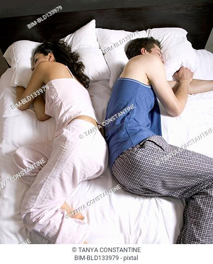 Couple sleeping back-to-back on bed