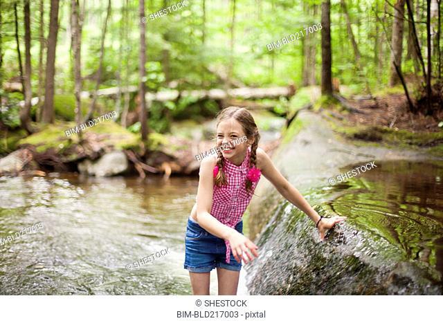 Caucasian girl laughing in river